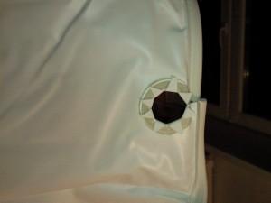 Отверстие в полотне натяжного потолка для крепления в месте расположения трубы центрального отопления
