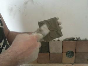 Начало укладки плитки на левой стороне стены