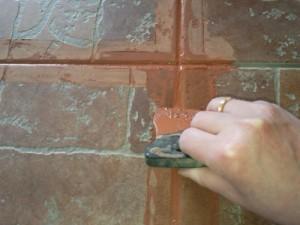 Заделка швов при помощи резинового шпателя между половыми плитками