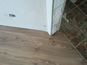 Уложенный ламинат в пространство между стеной, косяком дверного проема и стороной половой плитки в каридоре