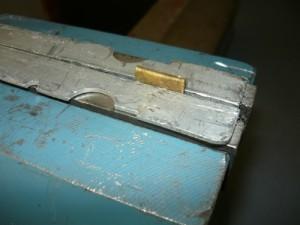 Пластина загнута и зажата в тисках через вставки