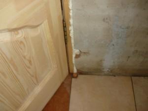 Вид на отколовшийся участок стены при креплении дверной коробки деревянной двери