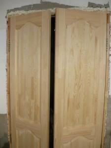 Установленная двухстворчатая деревянная дверь