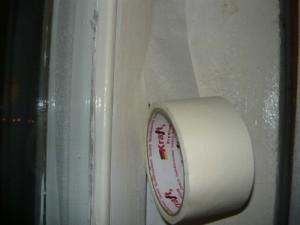 Оклейка щелей оконных рам при помощи бумажного скотча