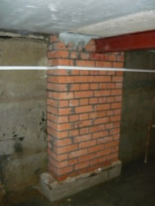Тумба из кирпича, выложенная вплотную к стене подвала