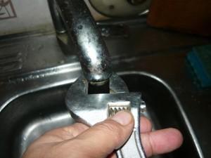 Отвинчивание фильтра крана при помощи разводного ключа