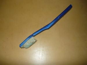 Старая зубная щетка, подрезанная наискось