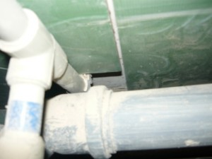 Вид сверху на обрезанную часть плитки при обходе труб канализации