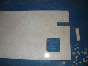 Выломанная часть плитки и полученное отверстие