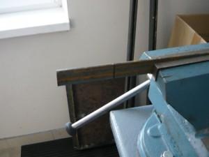 Зажатая металлическая полоса в тисках