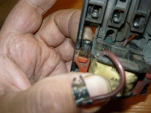 Придерживание пальцем пружины при установке блока контактов