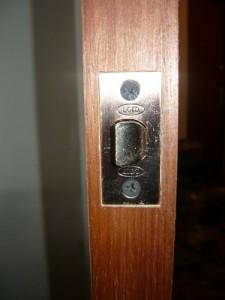 Вид на закрепленный замок в полости двери при помощи шурупов