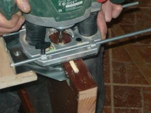 Вид на выборку отверстия в деревянной двери с помощью фрезера