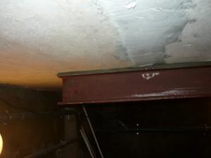 Вид на конец упорной металлической балки, поддерживающей бетонное перекрытие