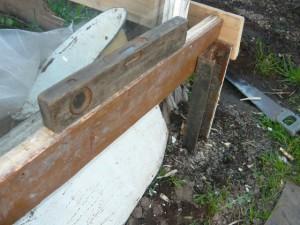 Выравнивание доски перед креплением доски на углу парника