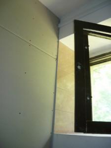 Вид на смонтированные листы гипсокартона возле оконного проема