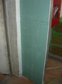 Вид на смонтированные листы гипсокартона возле дверного проема перегородки