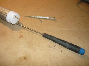 Выкручивание винтов крепления цоколя светодиодной лампы при помощи специальной отвертки