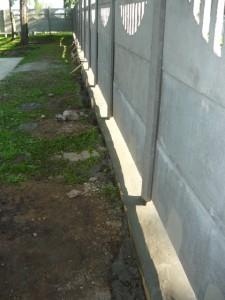 Вид на фундамент под бетонным забором слева