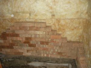 Обитая стена на фоне сложенных кирпичей