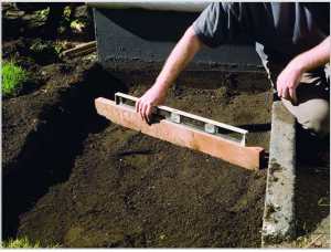 Заполнение приподнятой грядки грунтом и выравнивание поверхности с использованием уровня