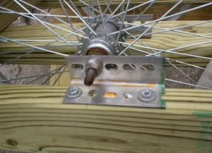 Вид на крепление оси колеса через отверстия в уголке